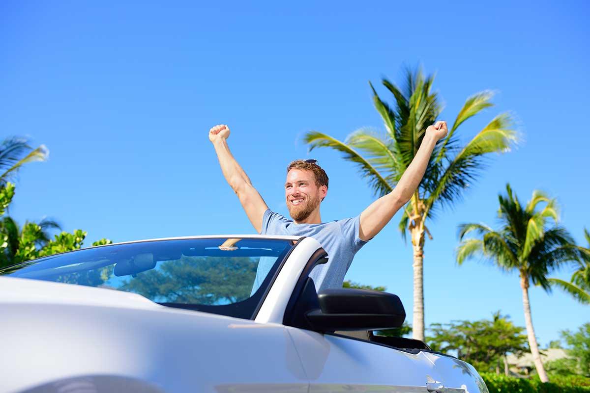 joven-levanta-sus-brazos-en-el-coche